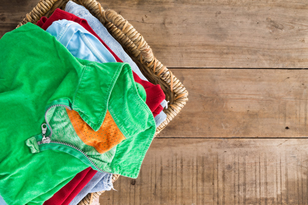 Clean washed unironed summer clothes with a fresh fragrance stacked in a wicker laundry basket with a bright green shirt on top overhead view on rustic wooden boards with copyspace to the right