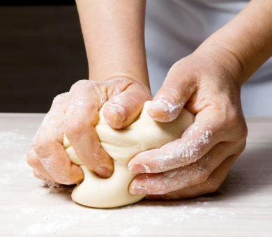 Woman's hands kneading bread dough in kitchen on wooden tab