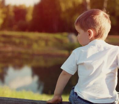 Junge sitzt am Fluss