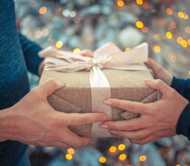 Hände überreichen Geschenk