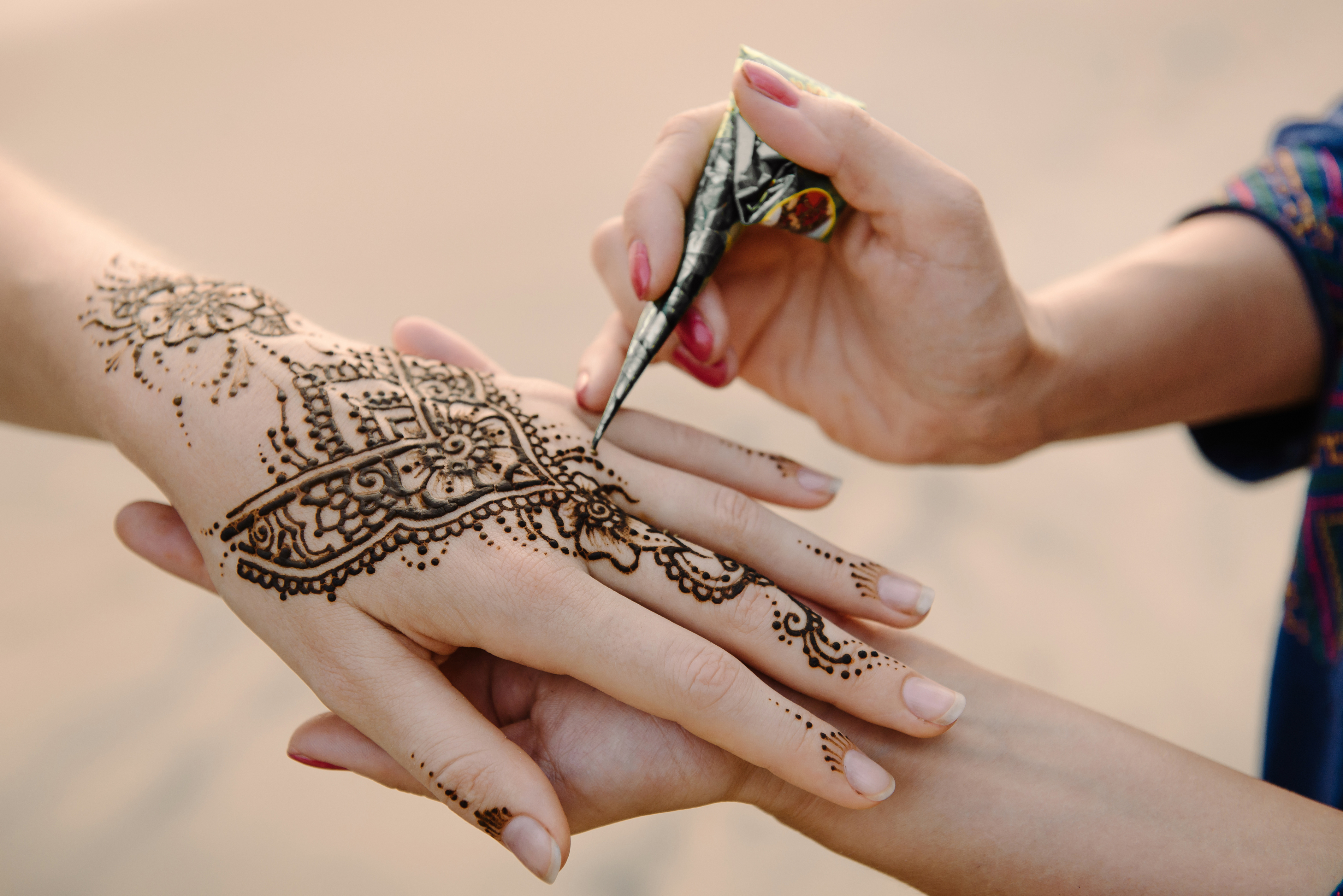 a woman getting a henna design