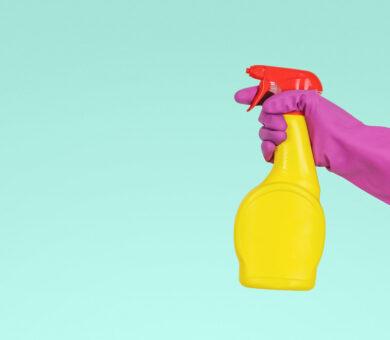 Eine Hand, die einen Gummihandschuh trägt, hält eine Sprühflasche