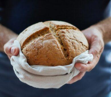zwei Hände halten ein ganzes Brot