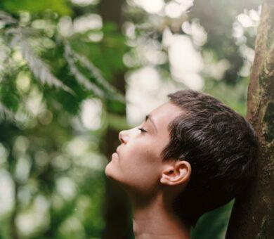 Frau lehnt an einem Baum im Wald und atmet