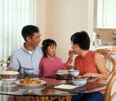 Eltern und Kind sitzen am Esstisch