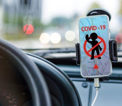Ein Smartphone, das in einer Halterung neben einem Autolenkrad befestigt ist zeigt ein durchgestrichenes Männchen. Darüber steht COVID-19.