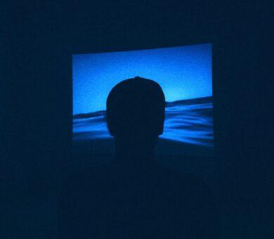 Person steht vor einer Leinwand die blaues Wasser zeigt