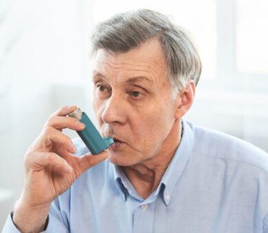 Senior Man Using Asthma Inhaler For Allergies
