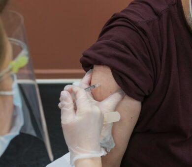 Ärztin setzt eine Spritze an einen Arm